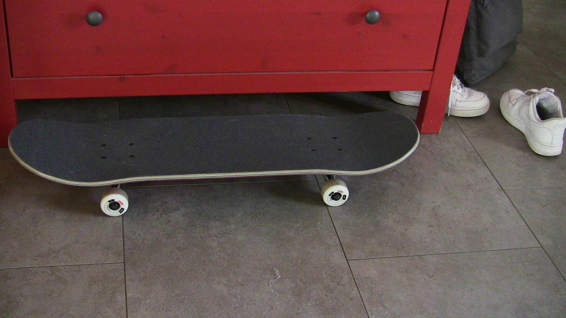 Skateboard vor rotem Schränkchen