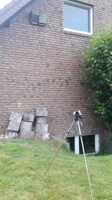 Videokamera auf Stativ vor Hauswand mit Fledermauskästen